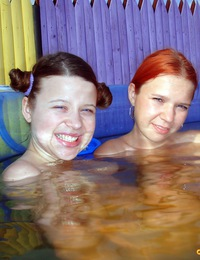 Two lesbian teens in a small pool caressing their bodies
